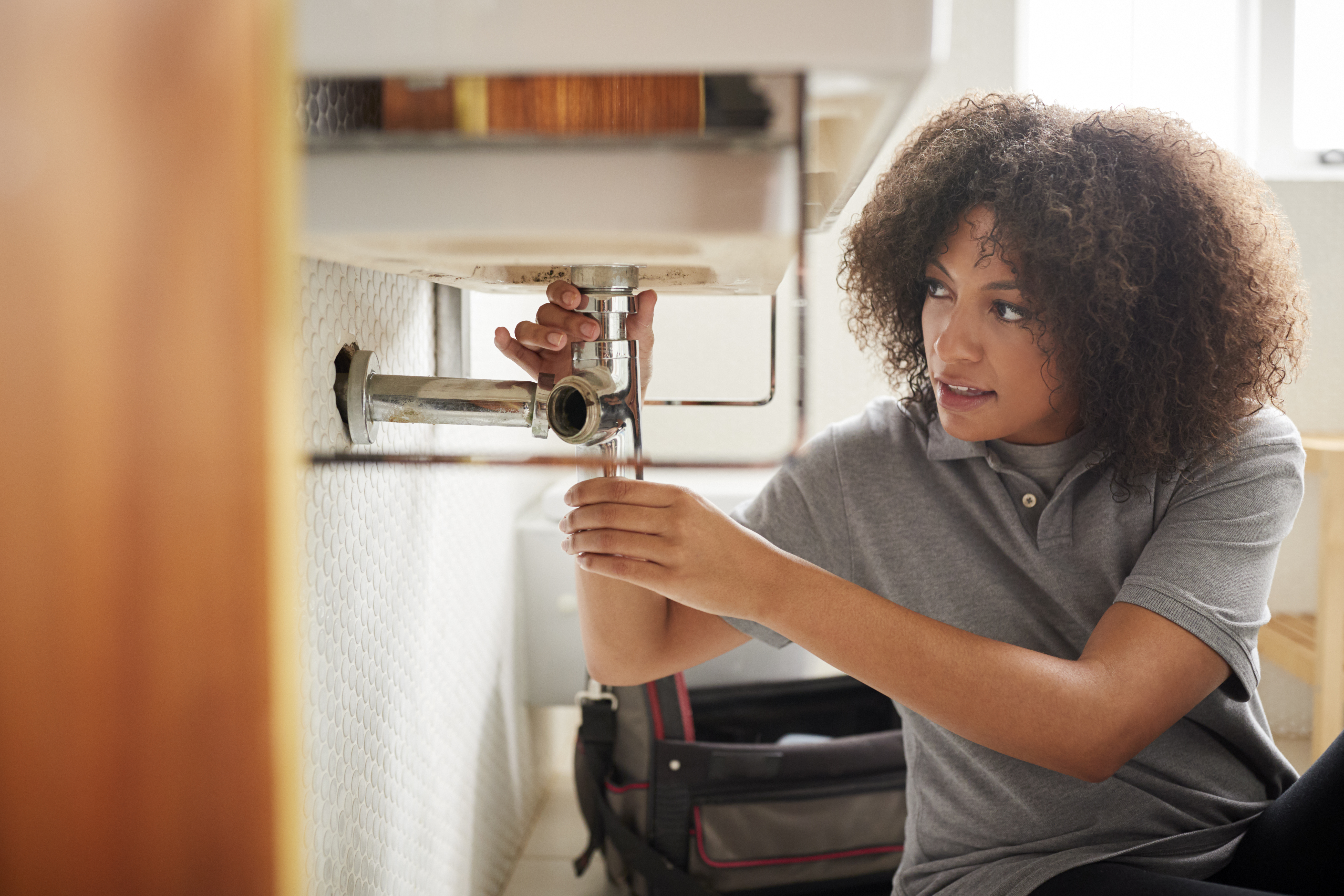 Young Black Female Plumber Fixing A Bathroom Sink