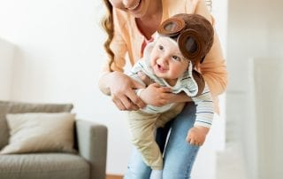 Mother with Baby Wearing Pilot Hat at Home